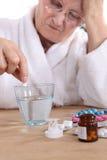 Femme supérieure prenant des pilules Photographie stock
