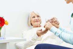 Femme supérieure prenant des pilules avec de l'eau Photos stock