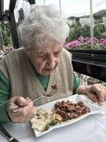Femme supérieure prenant le déjeuner dans un restaurant Photos libres de droits