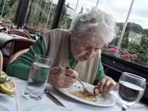Femme supérieure prenant le déjeuner dans un restaurant Images stock