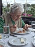 Femme supérieure prenant le déjeuner dans un restaurant Image stock
