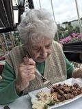 Femme supérieure prenant le déjeuner dans un restaurant Photo stock