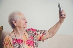 Femme supérieure prenant le selfie Photographie stock
