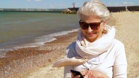 Femme supérieure prenant le selfie par le smartphone sur la plage banque de vidéos