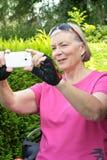 Femme supérieure prenant le téléphone de photo Photographie stock