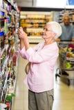 Femme supérieure prenant une photo de produit sur l'étagère Photo stock