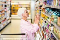 Femme supérieure prenant une photo de produit sur l'étagère Photos stock