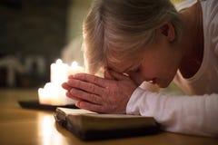 Femme supérieure priant, mains étreintes ensemble sur sa bible Image stock