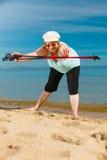 Femme supérieure réchauffant avec les poteaux de marche Photo libre de droits