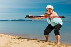 Femme supérieure réchauffant avec les poteaux de marche Photographie stock libre de droits