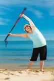 Femme supérieure réchauffant avec les poteaux de marche Image stock