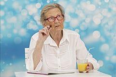 Femme supérieure résolvant des mots croisé sur une magazine tout en buvant du jus d'orange Photo stock