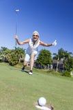 Femme supérieure heureuse jouant le golf et la mise Images libres de droits