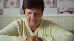 Femme supérieure regardant des pilules et des yeglasses sur le plan rapproché de table à la maison clips vidéos