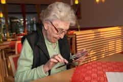Femme supérieure regardant l'écran de la tablette images stock