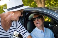 Femme supérieure regardant l'homme s'asseyant dans la voiture Photos libres de droits
