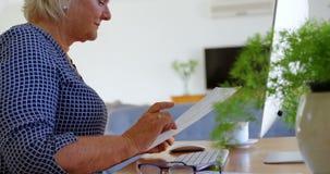 Femme supérieure regardant les documents à la maison 4k banque de vidéos