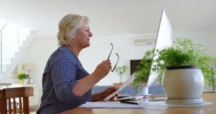 Femme supérieure regardant les documents à la maison 4k clips vidéos