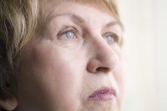 Femme supérieure regardant loin Photographie stock libre de droits
