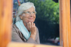 Femme supérieure regardant loin dans la boutique de café Photographie stock libre de droits