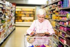 Femme supérieure regardant sa liste d'épicerie Image stock