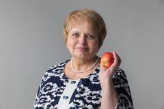 Femme supérieure restant avec la pomme Photographie stock