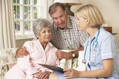 Femme supérieure retirée ayant le contrôle de santé avec l'infirmière At Home Photo stock