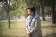 Femme supérieure sérieusement asiatique avec le bâton de marche Images stock