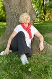 Femme supérieure s'asseyant à un arbre dans un jardin Photo stock
