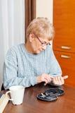 Femme supérieure s'asseyant au bureau et coupant des ongles de doigts images libres de droits