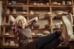 Femme supérieure s'asseyant sur la chaise avec des jambes sur la table contre des étagères avec des marchandises de poterie Photographie stock