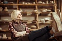 Femme supérieure s'asseyant sur la chaise avec des jambes sur la table contre des étagères avec des marchandises de poterie Photo stock