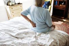 Femme supérieure s'asseyant sur le lit en douleur Photographie stock libre de droits