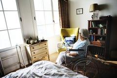 Femme supérieure s'asseyant sur seul le fauteuil roulant images libres de droits