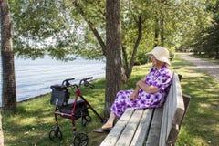 Femme supérieure s'asseyant sur un banc de parc Photos stock