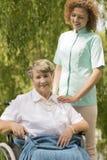 Femme supérieure s'asseyant sur un fauteuil roulant et une infirmière Image libre de droits