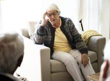 Femme supérieure s'asseyant sur un sofa images libres de droits