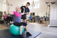 Femme supérieure s'exerçant sur la boule suisse avec des poids encouragé par l'entraîneur personnel In Gym photos stock