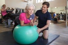 Femme supérieure s'exerçant sur la boule suisse encouragé par l'entraîneur personnel In Gym photographie stock libre de droits