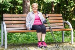 Femme supérieure se reposant après la marche nordique, modes de vie sportifs dans la vieillesse Photographie stock libre de droits