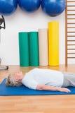 Femme supérieure se trouvant sur le tapis d'exercice Photographie stock