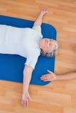 Femme supérieure se trouvant sur le tapis d'exercice Image libre de droits