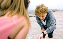 Femme supérieure semblant la montre intelligente avec l'entraîneur féminin Images stock