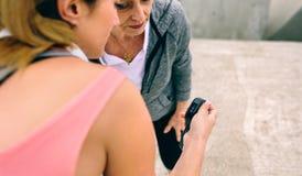 Femme supérieure semblant la montre intelligente avec son entraîneur Photographie stock libre de droits