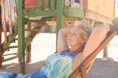 Femme supérieure semblant partie tout en détendant sur la chaise Photographie stock libre de droits