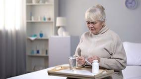 Femme supérieure seule prenant des pilules au centre médical, soins de santé dans la vieillesse images libres de droits