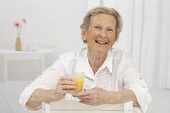 Femme supérieure smilling tout en buvant du jus d'orange Photos libres de droits