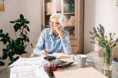 Femme supérieure songeuse comptant des impôts images stock