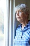 Femme supérieure souffrant de la dépression regardant hors de la fenêtre Images stock