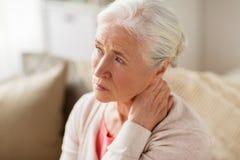 Femme supérieure souffrant de la douleur cervicale à la maison Photo stock